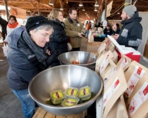 Maggie Gremore checks out Aunt Nee's fresh guacamole while Maureen and Jeff Van Hook make a purchase from Carlos Parisi during Linda Yellin's strolling culinary tour through Detroit's Eastern Market.